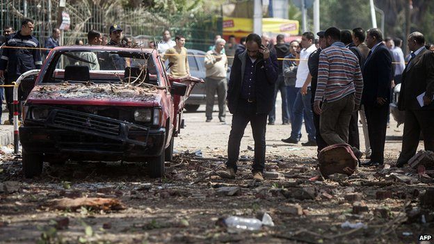 Egyptians inspect the damage after twin bombs struck police posts near Cairo University in the centre of Egypt's capital on April 2