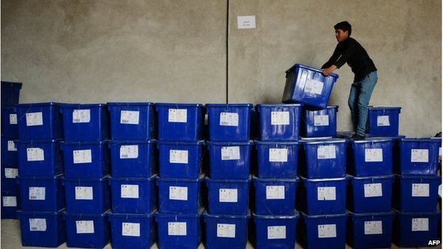 An Afghan election worker stands on a stack of plastic boxes containing election material at a warehouse in Mazar-i-Sharif
