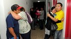People embrace on the top floor of a building in northern Chile where they gathered to avoid a possible tsunami