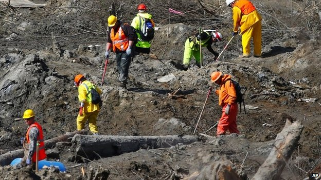 Workers dig at a much drier mudslide site on the west side at the west site of the mudslide on Highway 530 near mile marker 37, near Oso, Washington  on 1 April 2014