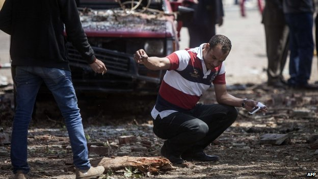 Investigators at the site of the bombings outside Cairo university (2 April 2014)