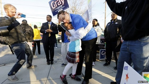 Washington DC Mayor Vincent Gray hugs 7-year-old Monae Rucker  at the precinct 65 polling place on the Lasalle-Backus Education Campus, in Washington 1 April 2014