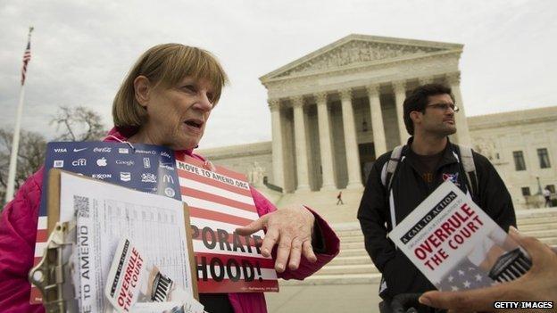 Joan Stallard (left) of Washington DC talks in front of the US Supreme Court in Washington DC 2 April 2014