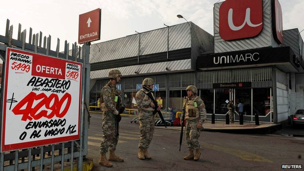 Soldiers guard a supermarket in Iquique on 2 April 2014