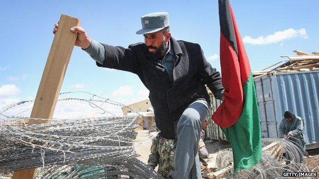 An Afghan National Police (ANP) officer loads concertina wire, which will be used to secure polling places ahead of presidential elections
