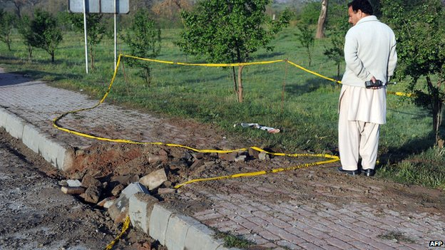 A Pakistani plainclothes security official inspects the site of a bomb explosion in Islamabad on 3 April 2014.