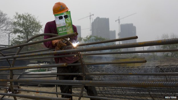 A labourer, wearing an improvised protective mask, welds steel bars at a residential construction site in Quzhou, Zhejiang province on 3 April  2014.