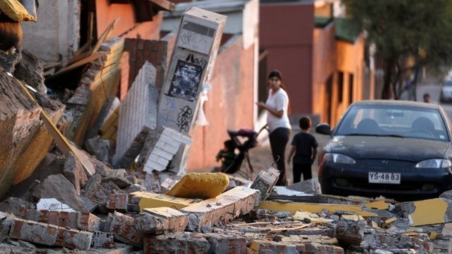 A resident looks at debris around a home after an earthquake and tsunami hit the northern port of Iquique April 2, 2014
