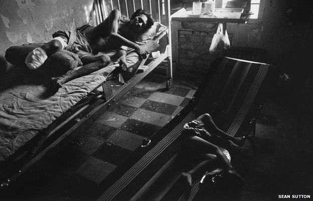 As his daughter sleeps nearby, a man lies in hospital recovering from a leg amputation following a landmines accident. Cambodia, 1996