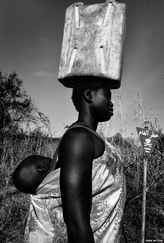 Maria walks through a minefield to get water from a nearby stream every day, South Sudan's Central Equatoria region, 2013