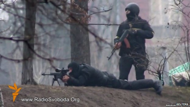 A riot policeman stands close to a sniper in Kiev, 20 February