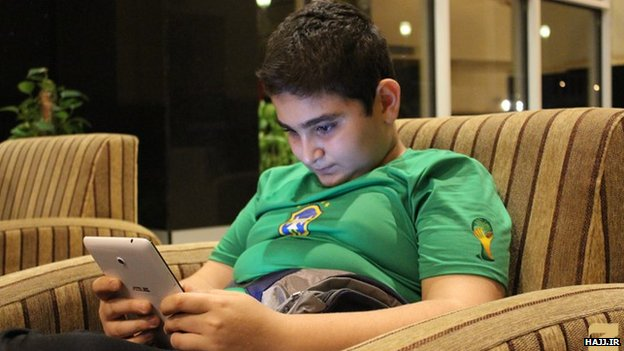 A boy plays on his tablet in a hotel lobby