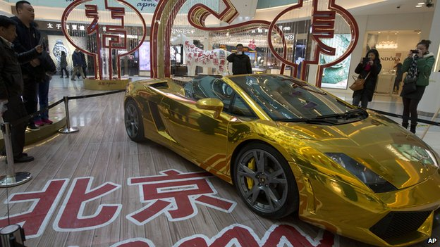 A gold Lamborghini luxury sports car is displayed at a mall with a price tag in Beijing, China,  on 17 February 2014
