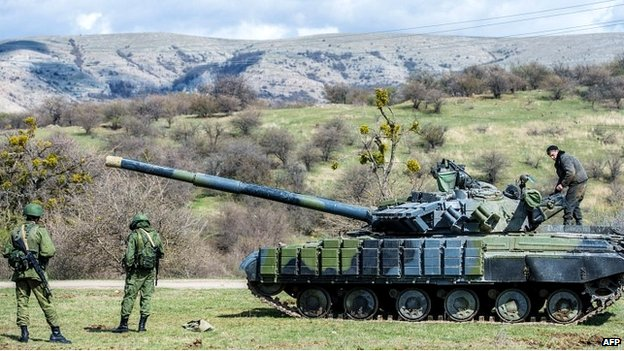 Russian soldiers stand near a tank outside a former Ukrainian military base in Crimea - 27 March 2014