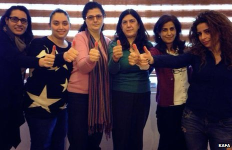 Six Lebanese women with red thumbs outstretched