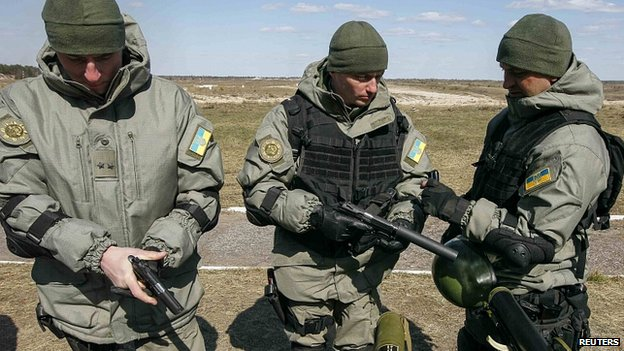 Ukrainian soldiers check pistols during military exhibition near settlement of Desna in Chernigov region.