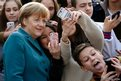Pupils take mobile phone selfies with German Chancellor Angela Merkel