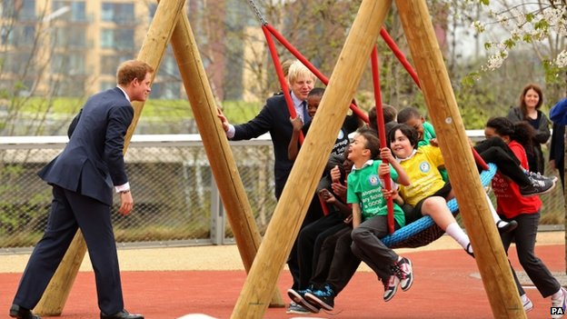 Mayor of London Boris Johnson watches as Prince Harry pushes school children on a swing during a visit to the new Queen Elizabeth Olympic Park