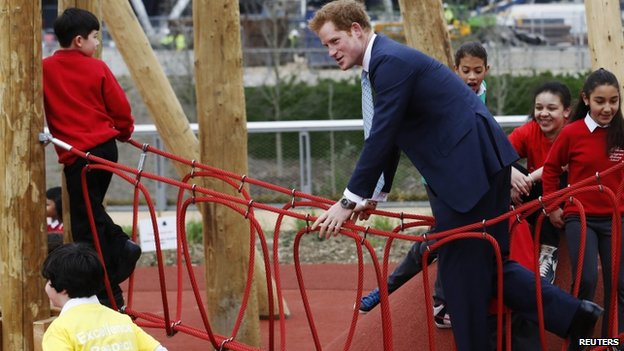 Prince Harry plays on a rope bridge with children