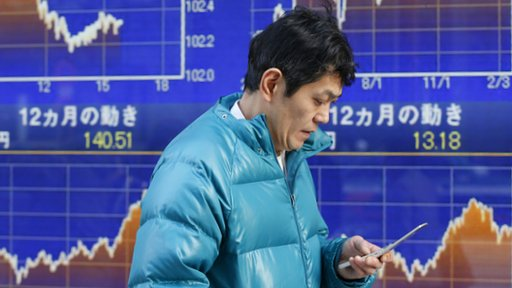 Man checks his phone in front of graphs from the stock market