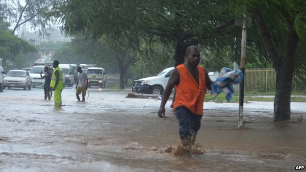A man walks through flood waters in the Solomon Islands capital of Honiara on 4 April 2014.