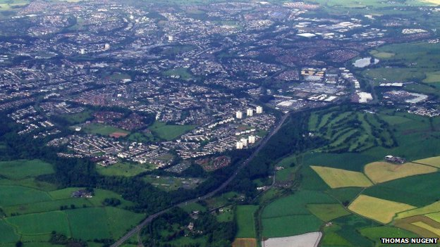 Looking along the A725 from Hamilton. The course if the former railway line from Hamilton to East Kilbride can be seen to the left of the white field near the bottom of the photo.
