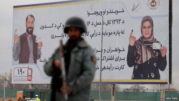 Afghan policeman stands by an election billboard in Kabul on 4 April 2014