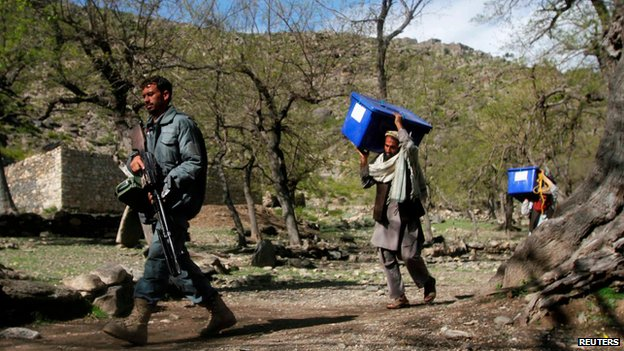 Afghan policeman walks with election workers carrying ballot boxes in Darenoor, Nangarhar province, on 4 April 2014