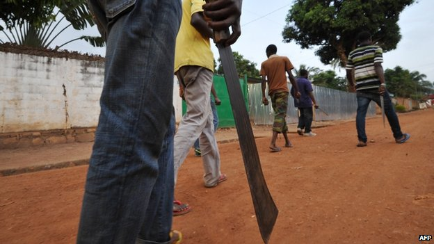 Young people with machetes patrol in their district in Bangui, CAR, on 12 March 2014