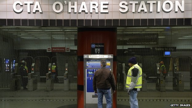 Chicago Transit Authority workers stand outside O'Hare International Airport station shortly after the crash (24 March 2014)