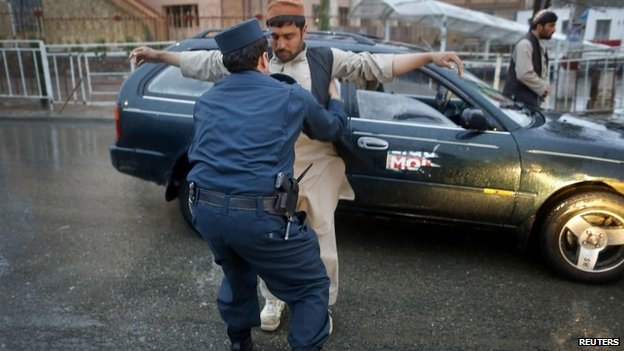 A policeman checks a motorist at a road block on election day in central Kabul