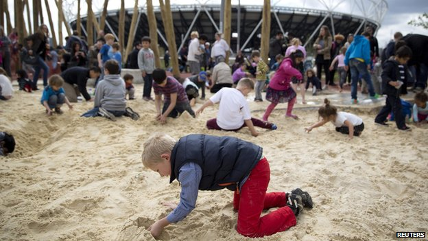 Children can play in a sandpit in front of the Olympic Stadium at the park