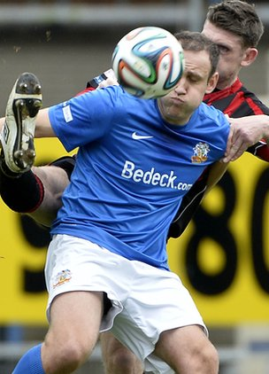 Glenavon striker Guy Bates shields the ball from Paul Leeman