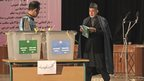 Afghan President Hamid Karzai, right, walks to the ballot boxes to cast his vote at Amani high school in Kabul