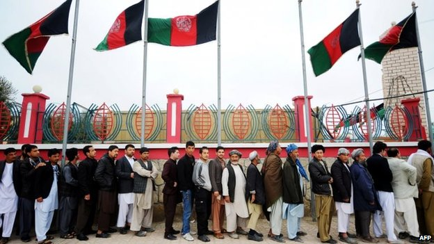 Afghan residents wishing to vote line up underneath underneath Afghan flags outside a polling station in Mazar-i-Sharif