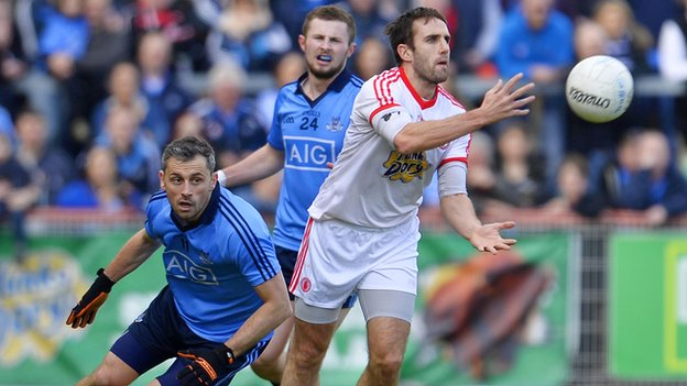 Mark Donnelly gets the ball away despite Alan Brogan's attentions