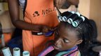 A hairstylist attends to a client in Lagos, Nigeria, on 2 April 2014