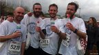 Runners drinking water at the finishing line.