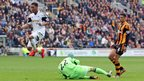 Hull City keeper Steve Harper dives low to deny the advancing Swansea City midfielder Jonathan de Guzman.