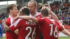 Wrexham players mob Johnny Hunt after his early goal against Macclesfield, which earned Kevin Wilkin his first win in charge.