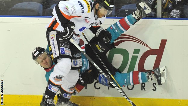 Belfast Giants player Gareth Roberts takes a tumble from Gord Baldwin's challenge in the play-off final