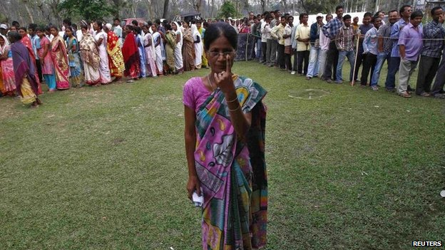 A woman shows her ink-marked finger after casting her vote as others line up to cast their ballot at a polling station