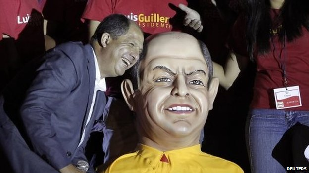 Luis Guillermo Solis poses next to a figure of himself before delivering a speech at a rally after official election results were released in San Jose on 6 April, 2014
