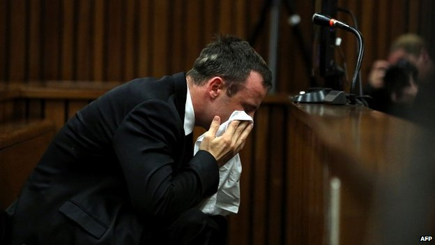 Oscar Pistorius wipes his face during his murder trial in Pretoria - 7 April 2014