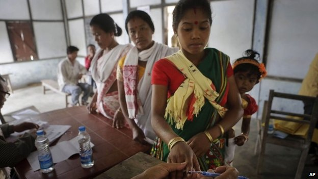 An election officer applies indelible ink mark on the finger of a Mishing tribal woman voter during the first phase of elections at Misamora Sapori, an island in the River Brahmaputra in the northeastern Assam state, India, Monday, April 7, 2014.