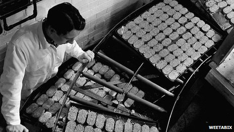 A factory worker checking the quality of biscuits in the Weetabix factory