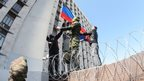 "Pro-Russian activists in Donetsk hoist a flag representing their ""people's republic""."