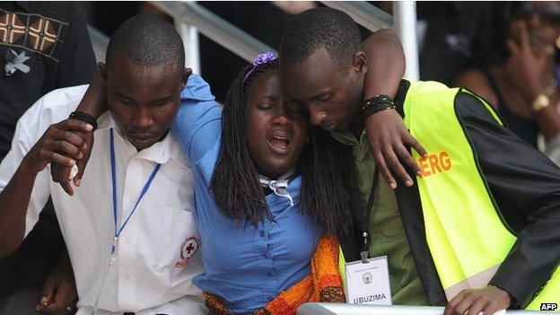 A woman is helped out of the Amahoro stadium, in Kigali, on April 7,2014, during a ceremony marking the 20th anniversary of Rwanda's genocide.