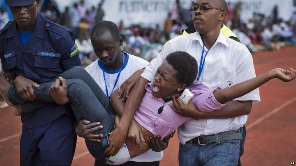 A wailing and distraught Rwandan woman is carried away to receive help during a public ceremony to mark the 20th anniversary of the Rwandan genocide in Kigali on 7 April 2014