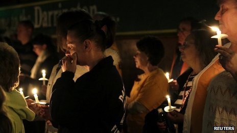 People participate in a candlelight vigil at the Community Center in Darrington, Washington, on 5 April 2014